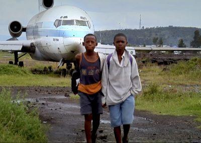 Children walking by a plane