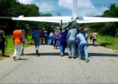 People helping to push plane down runway