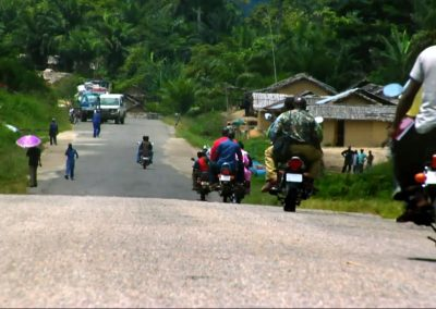 Motorcycles traveling down a dirt road